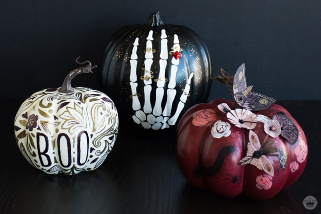 Three painted pumpkin designs: Doodled BOO, glam hand, abstract garden