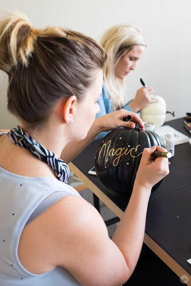 "Artist writing the word ""magic"" in script on a black pumpkin"