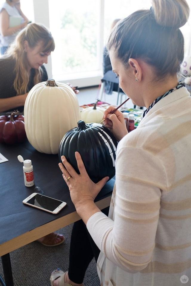 Artist painting a skeleton hand on a black pumpkin