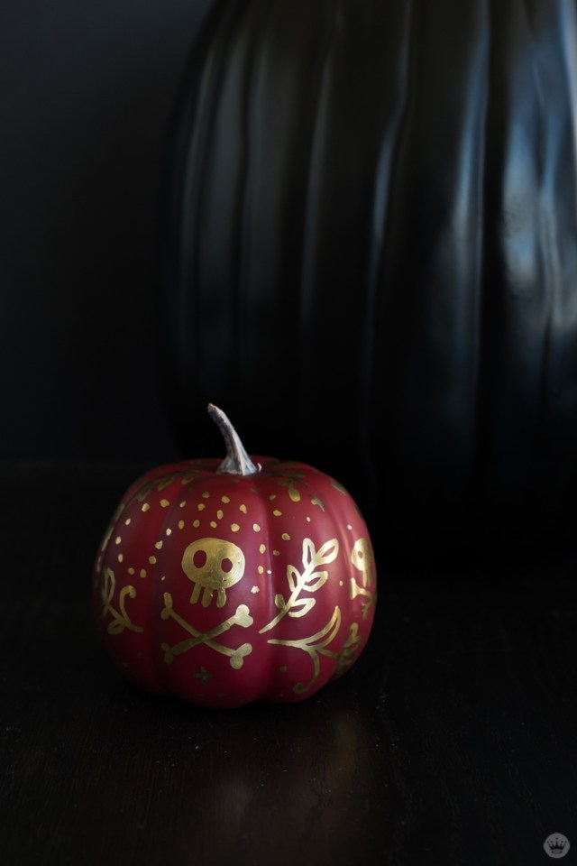 Elegant pumpkin designs: Small red pumpkin covered in metallic gold doodles, including skull and crossbones
