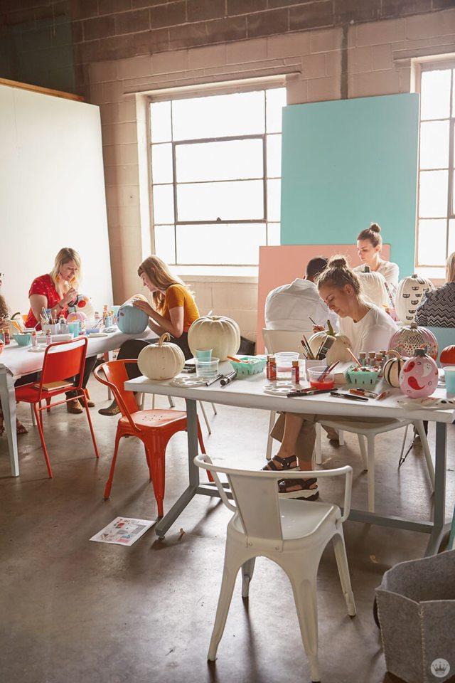A studio full of Hallmark artists painting pumpkins