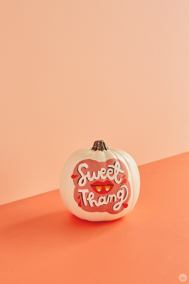 "Pumpkin painted with the words ""Sweet Thang"" and a mouth with candy corn fangs"