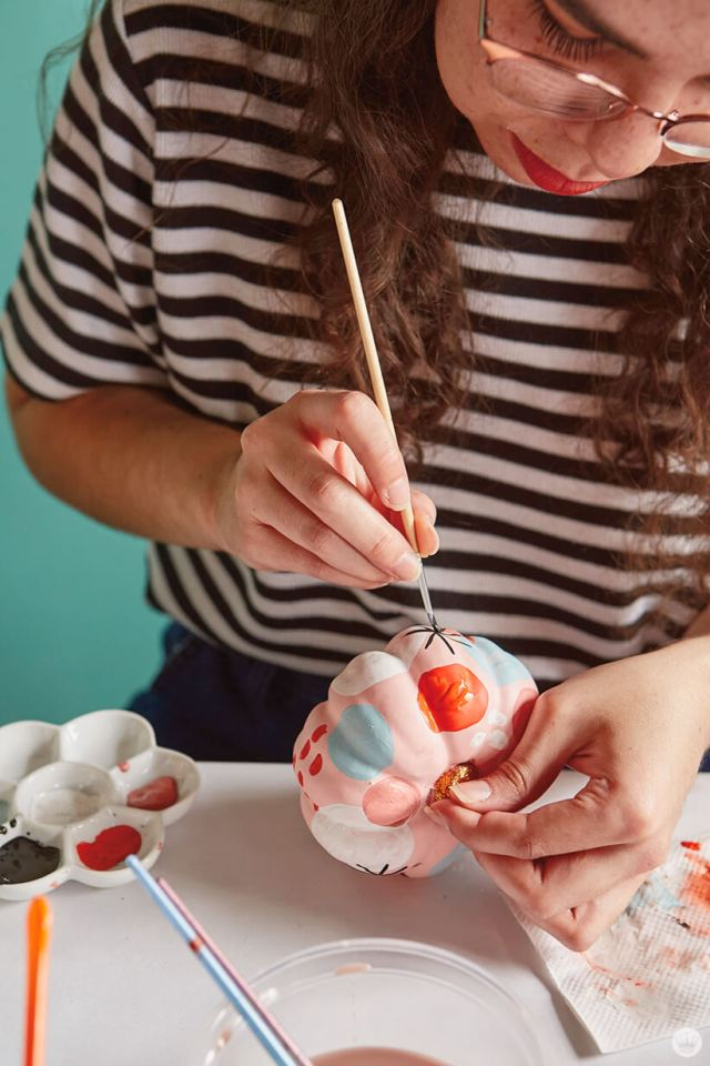 Alyssa G. paints a small pumpkin