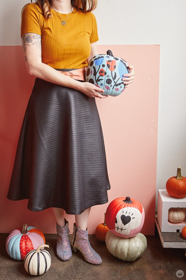 Artist posing with painted pumpkins