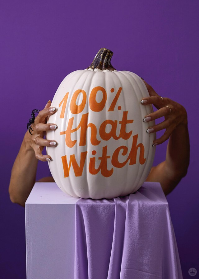 Hands holding 100% that witch pumpkin