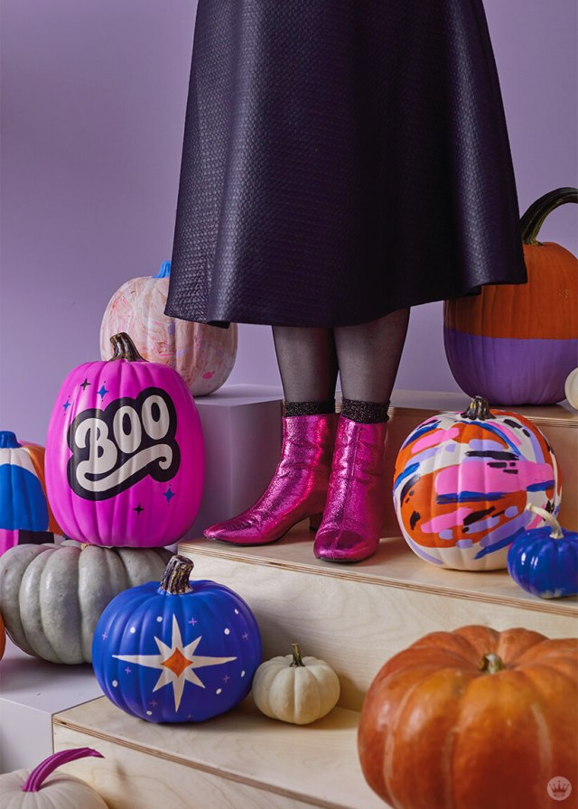 Woman in black skirt and pink metallic boots surrounded by painted pumpkins