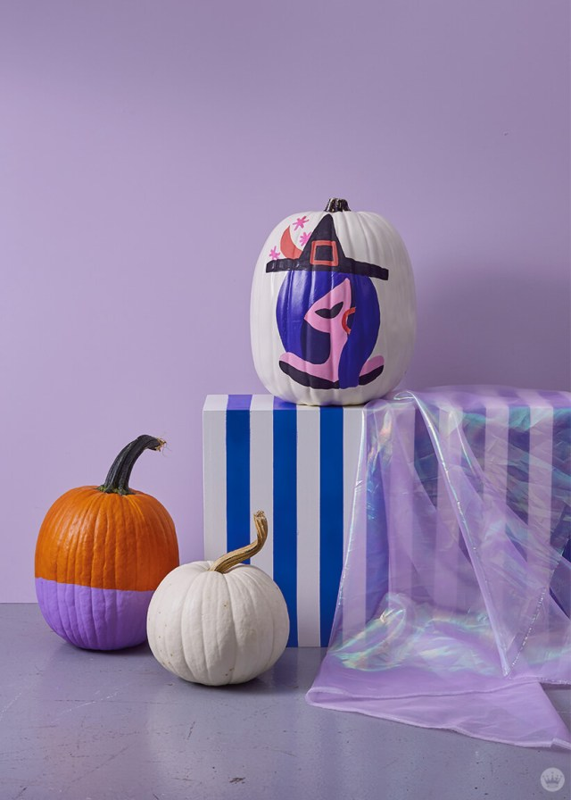 Pumpkin design featuring a witch with a hoop earring, along with a natural white pumpkin and orange pumpkin with lavender bottom