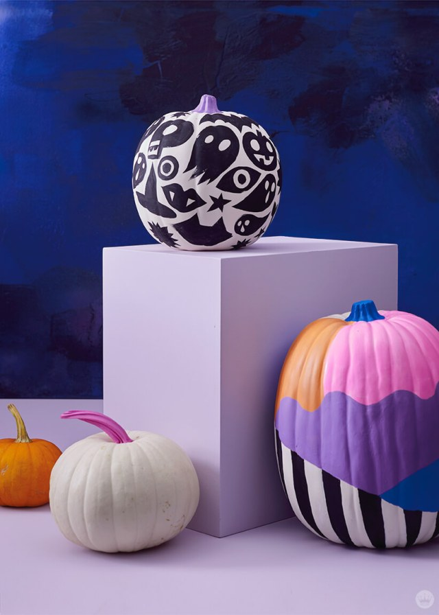 Pumpkins decorated with graphic designs in black, white, pink, and purple
