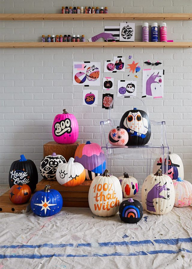 Painted pumpkins displayed with sketches and supplies