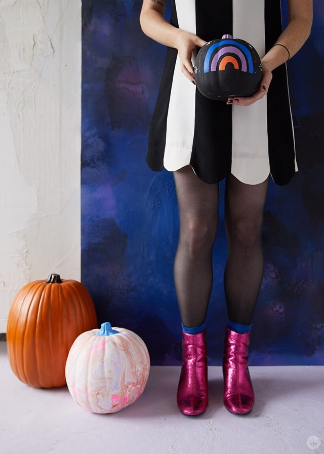 Artist in black and white striped dress and metallic pink boots displaying painted mini-rainbow pumpkin