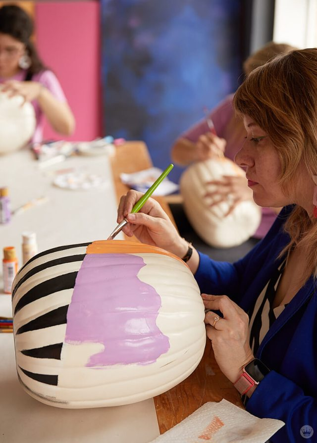 Free-hand painting shapes on a pumpkin
