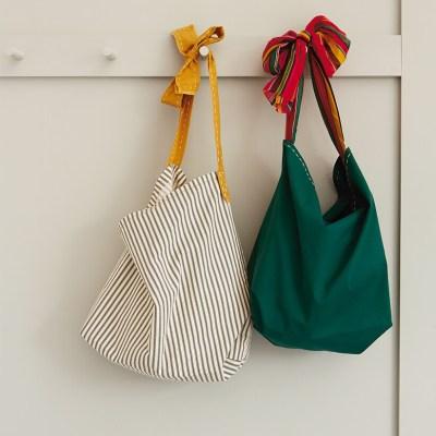 two Reusable Tote Bags hanging on a peg wall | thinkmakeshareblog.com