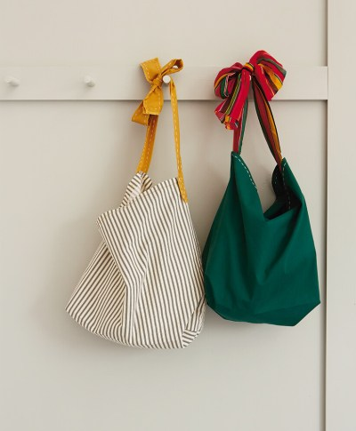two Reusable Tote Bags hanging on a peg wall | thinkmakeshareblog.com