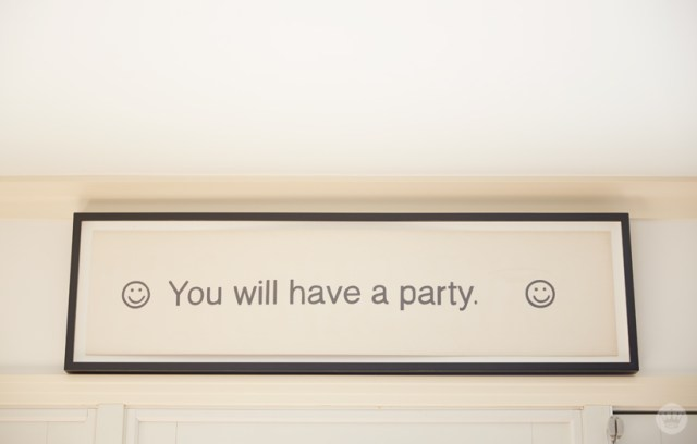 """Tips for displaying art: A framed print above a doorway says, """"You will have a party"""""""