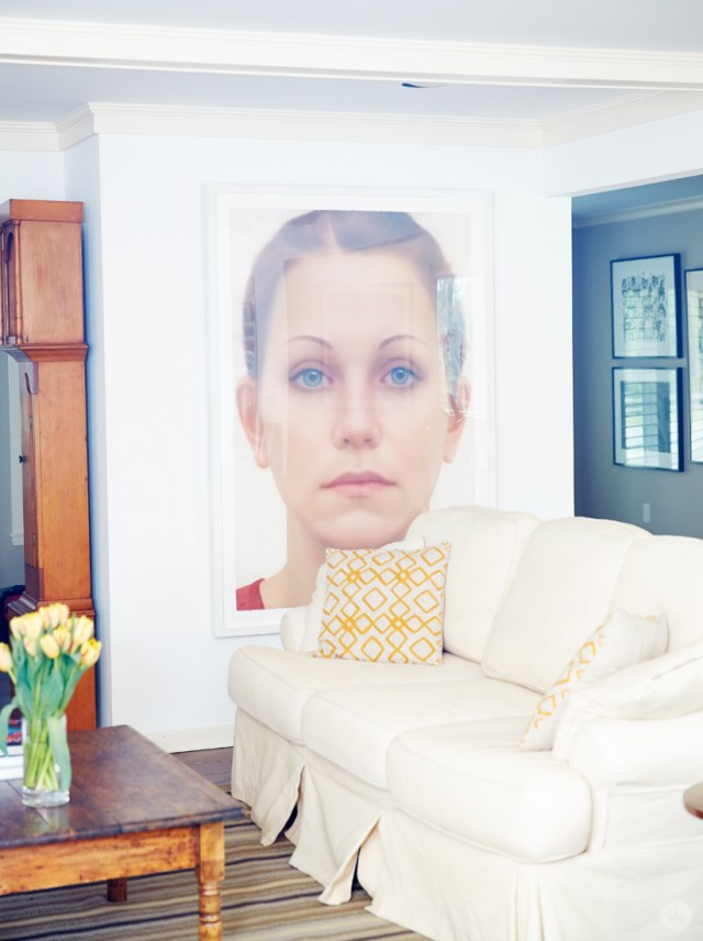 Tips for displaying art: A large framed portrait of a woman's face hangs next to a white sofa with yellow and white patterned pillows