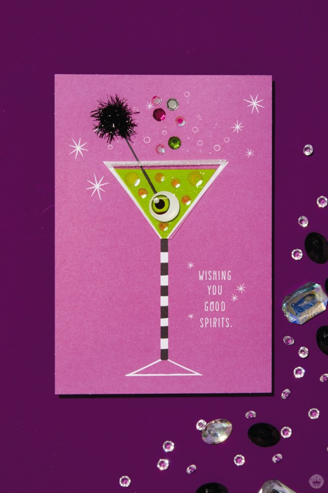 "The Signature card behind our signature Halloween cocktail, the Apple of My Eye-tini: Shimmery fuschia card featuring and black-and-white-stripe-stemmed martini glass filled with green liquid, garnished with an eyeball on a black cocktail pick (includes the message ""WISHING YOU GOOD SPIRITS"")"