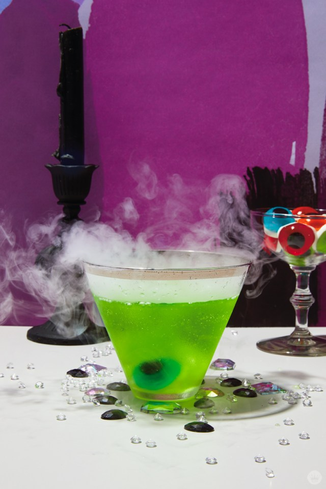 Signature Halloween Cocktails: The Apple of My Eye-Tini (green liquid in a stemless martini glass, garnished with eyeball candy and billowing with dry ice smoke)