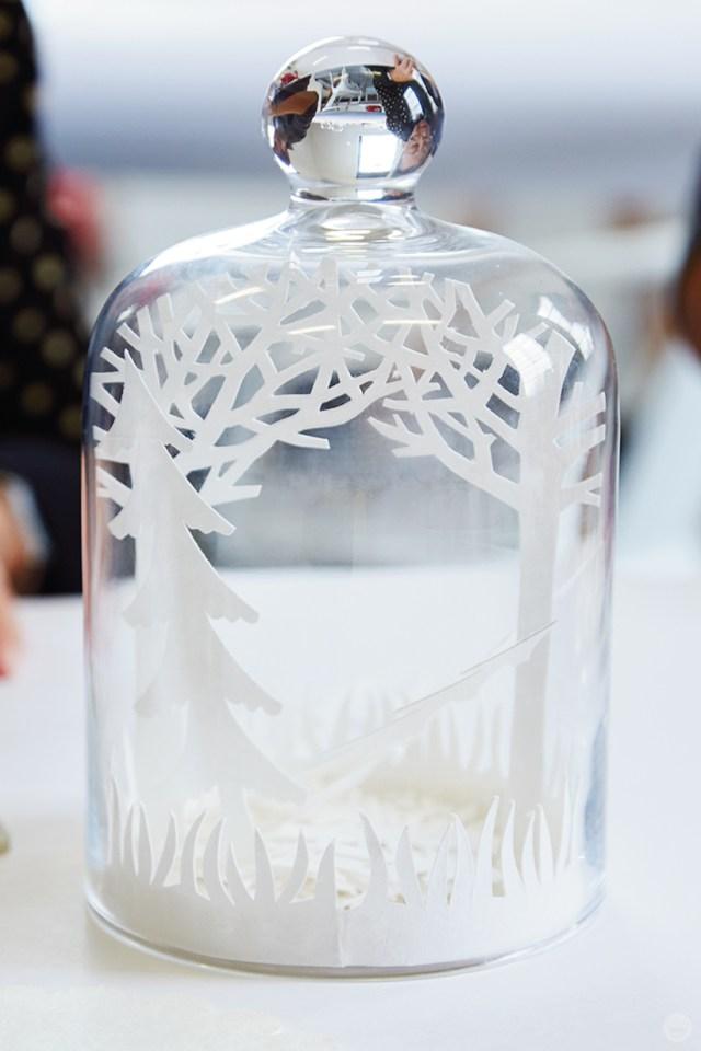 A cut paper winter scene inside a glass dome