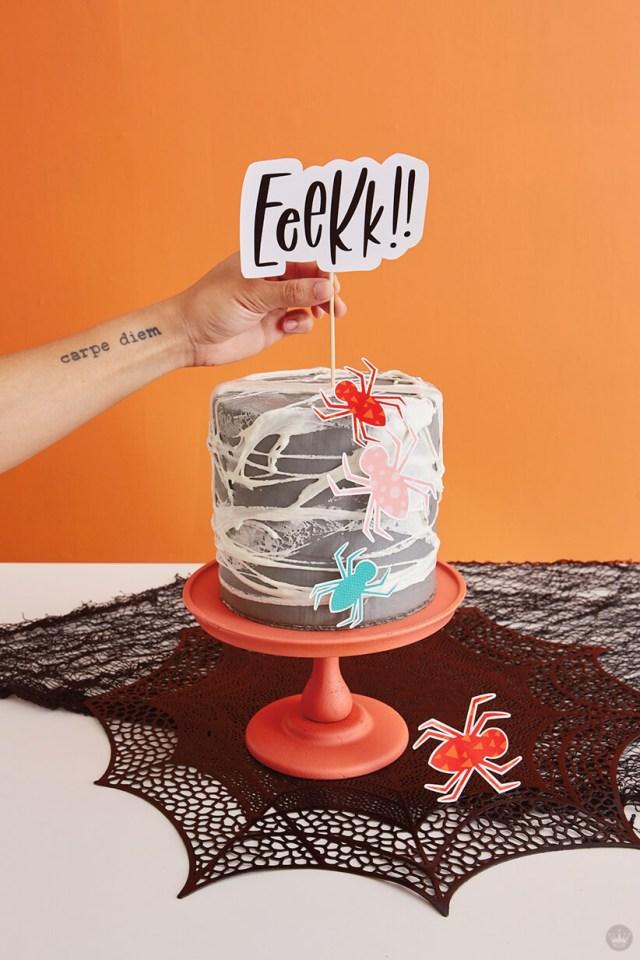 Adding Eeekk!! topper to spiderweb cake