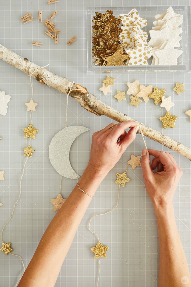 tying a string of stars to a large wood stick for the DIY Star Wall Hanging | thinkmakeshareblog.com