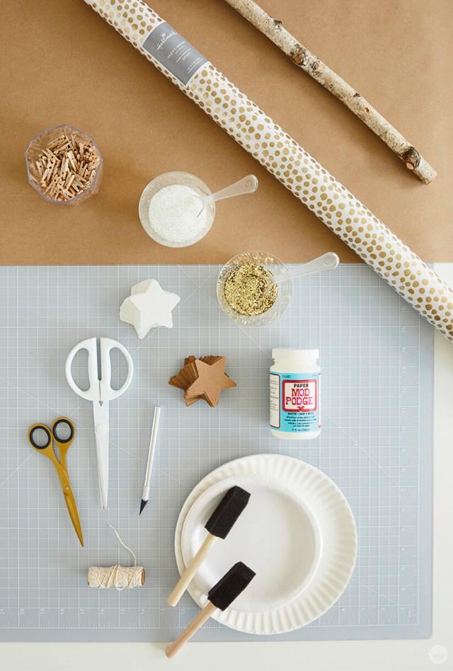 Fournitures pour la décoration murale DIY Star: branche, papier d'emballage, mini épingles à linge, colle artisanale, paillettes, étoiles en papier, ciseaux, couteau artisanal, ficelle, assiettes en papier, brosses en mousse | thinkmakeshareblog.com