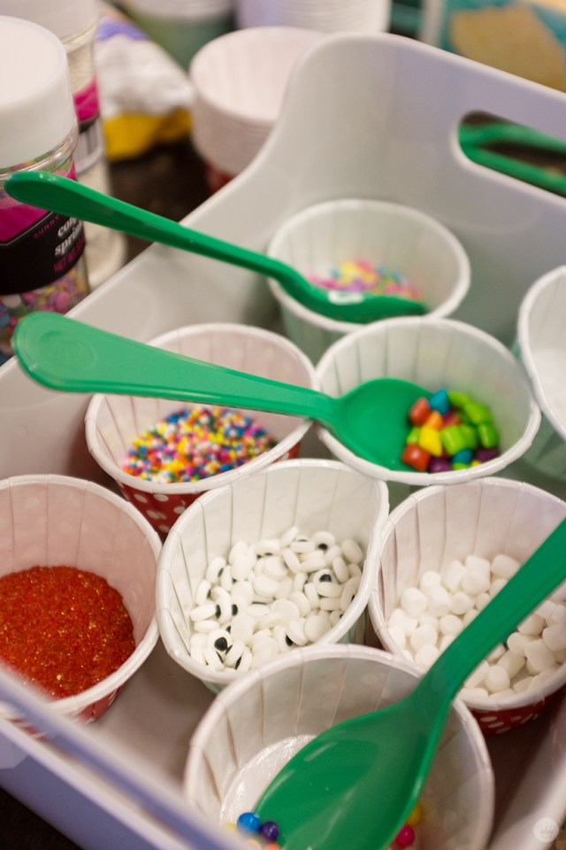 Paper cups full of sanding sugar and candy decorations