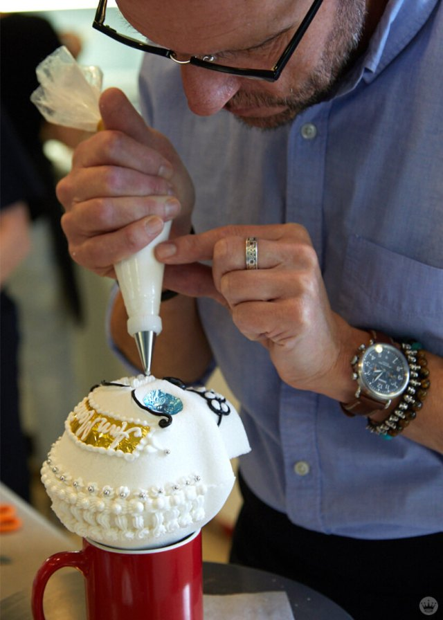A sugar skull being decorated by a Hallmark Artist