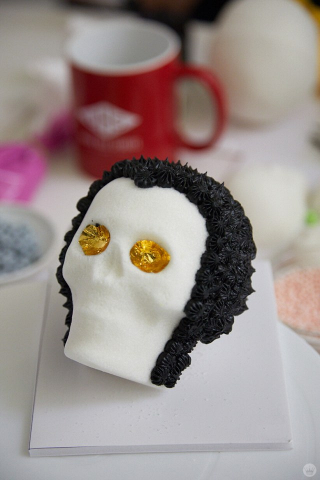 A sugar skull being decorated to look like Elvis