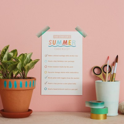 a table with the Crafter's Summer Checklist taped to the wall with a plant and cup of art supplies and washi tape on the table next to it | thinkmakeshareblog.com