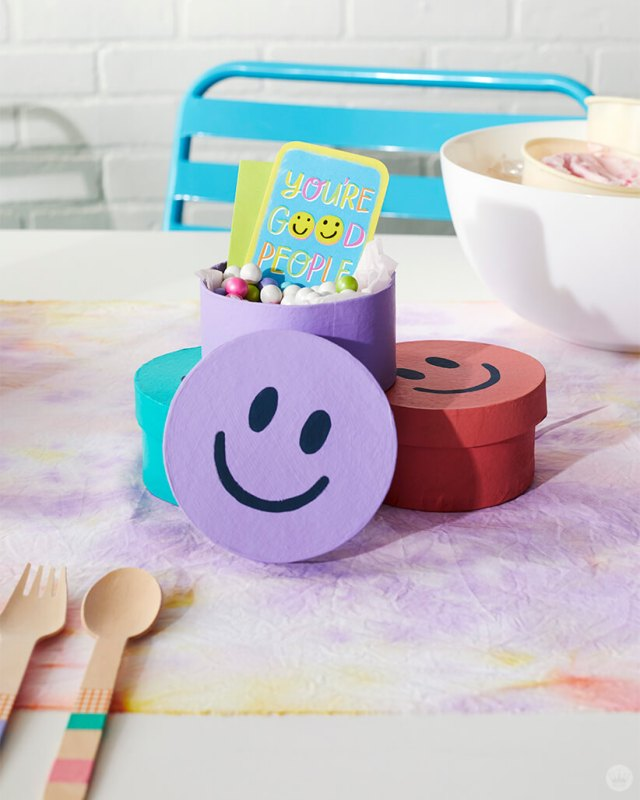 Round lavender, blue and pink treat boxes with painted-on smiley faces.