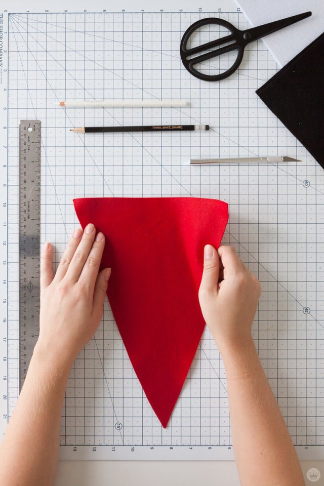 Cutting red felt into a triangle for a DIY Felt Pennant Banner