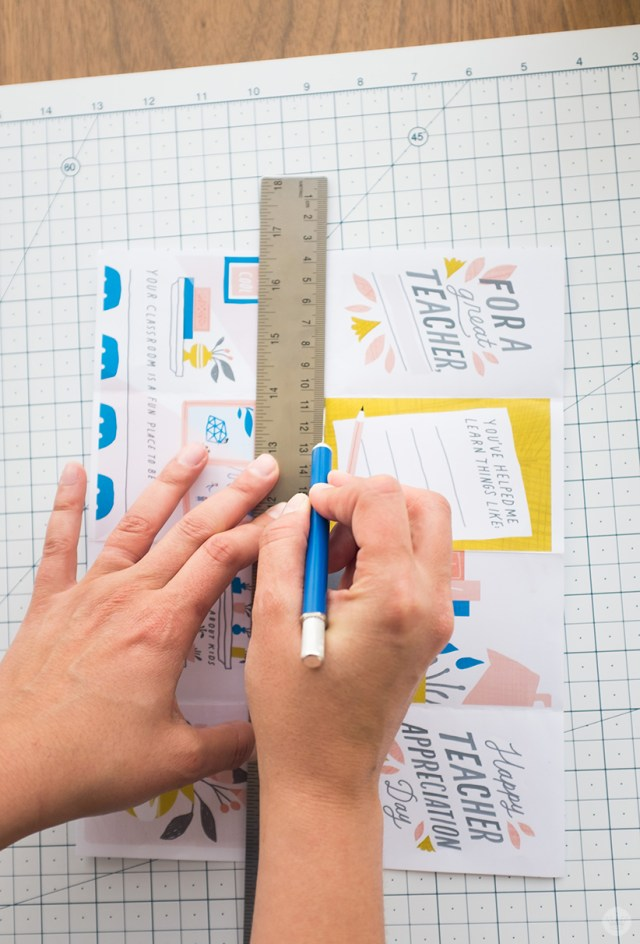 Using ruler and craft knife to cut center panels of DIY teacher appreciation zine along horizontal crease.