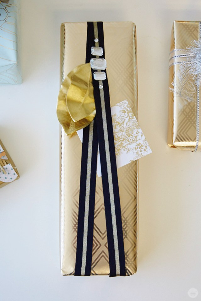 Gold-wrapped wedding gift with black ribbon, gold leaves and gems.