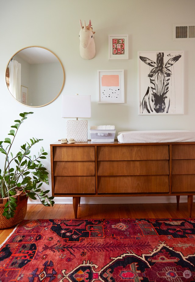 Tips for displaying art: A gallery wall over a mid-century modern buffet features a mirror, framed prints, and a textile sculpture of a unicorn bust