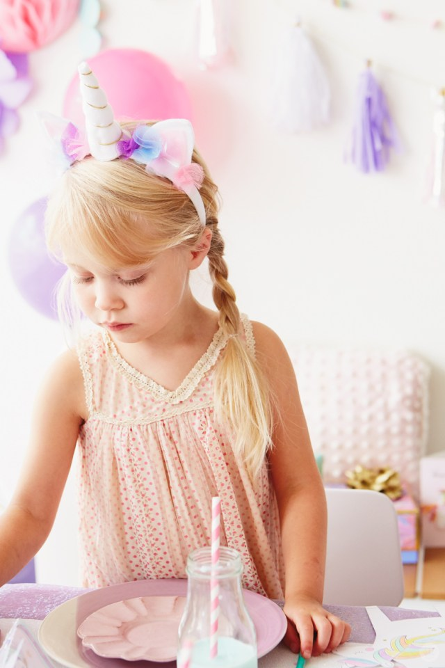 Girl wearing headband decorated with unicorn horn and ears