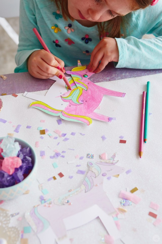 Girl coloring unicorn paper craft with colored pencils