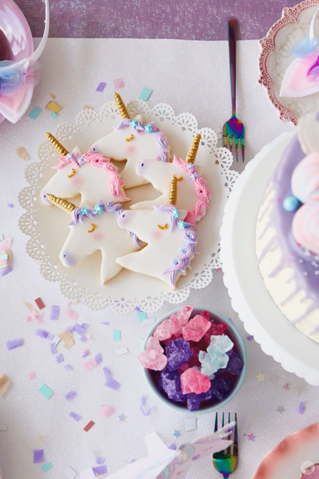 White lace-edged plate holding unicorn cookies; bowl with rock candy in pink, purple, and blue