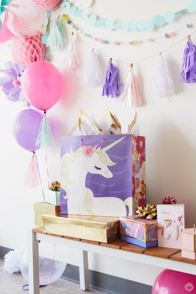 Stack of birthday gifts in Hallmark gift wrap; balloons and garlands as backdrop