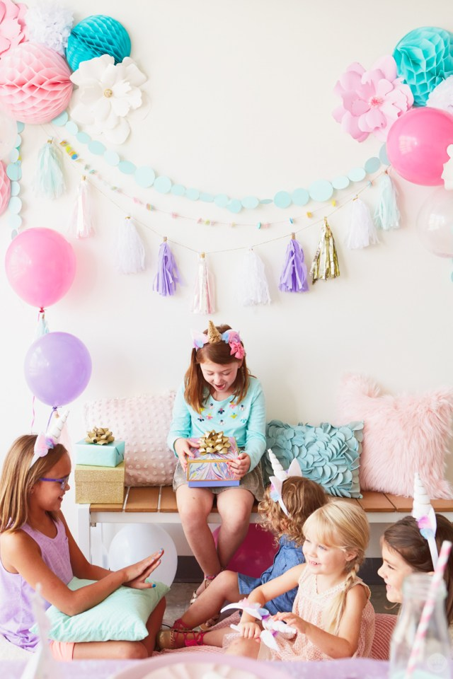 Girl opening presents at Unicorn birthday party