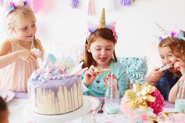 Girls at table with cake, eating unicorn cookies