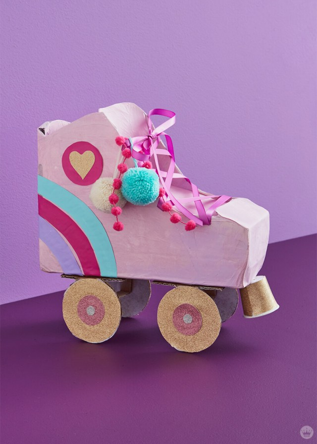 Pink Roller Skate kids' valentine box with rainbow stripes and pom-poms| thinkmakeshareblog.com