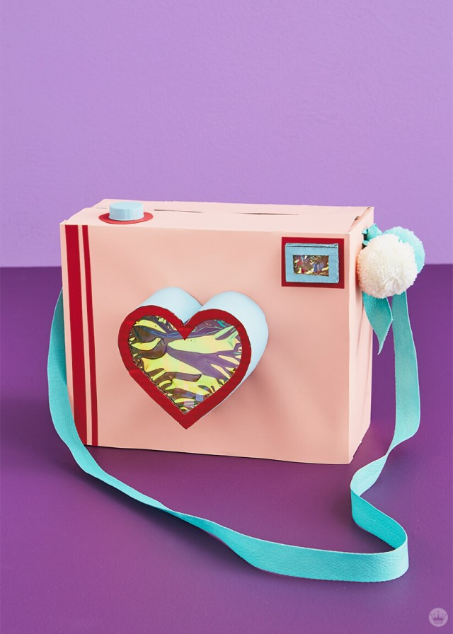Pink camera Valentine's Day mailbox with heart-shaped lens and pom-poms on strap | thinkmakeshareblog.com