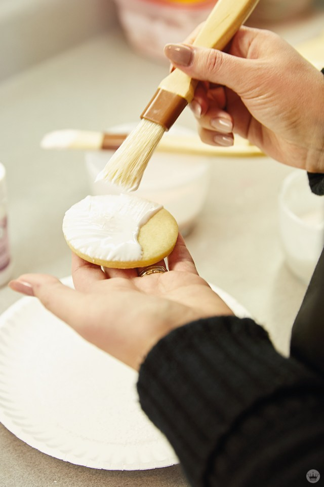 Painting royal icing onto a sugar cookie