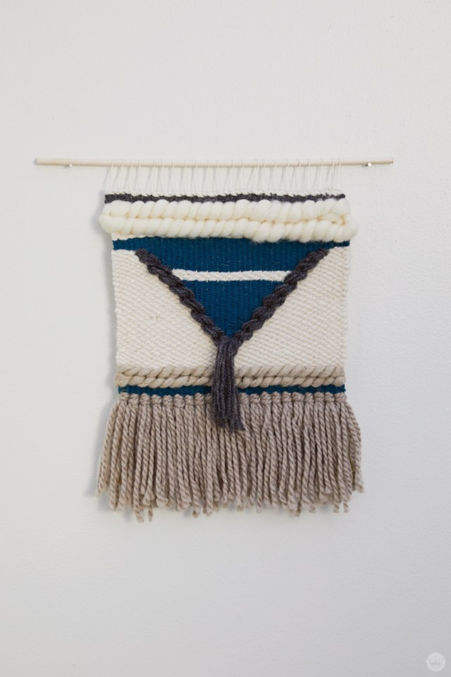 Weaving workshop: finished piece of fiber art with tassels and roving