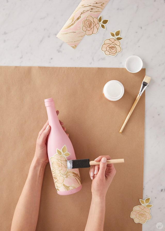 Upcycled wine bottle: Gluing wrapping paper designs to wine bottles | thinkmakeshareblog.com