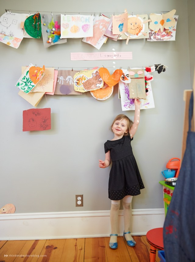 Tips for displaying art: A little girl in a black dress points at clips on cables displaying pieces of art she made