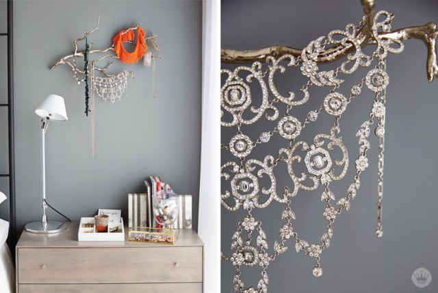 Tips for displaying art: Beaded and gemstone necklaces draped over a metallic branch, displayed above a nightstand