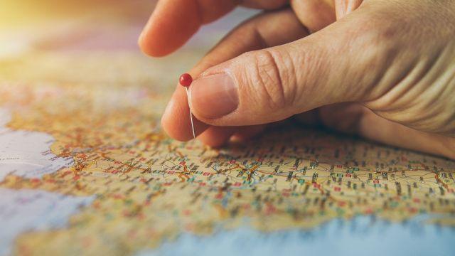 Mano che mette una puntina su una mappa