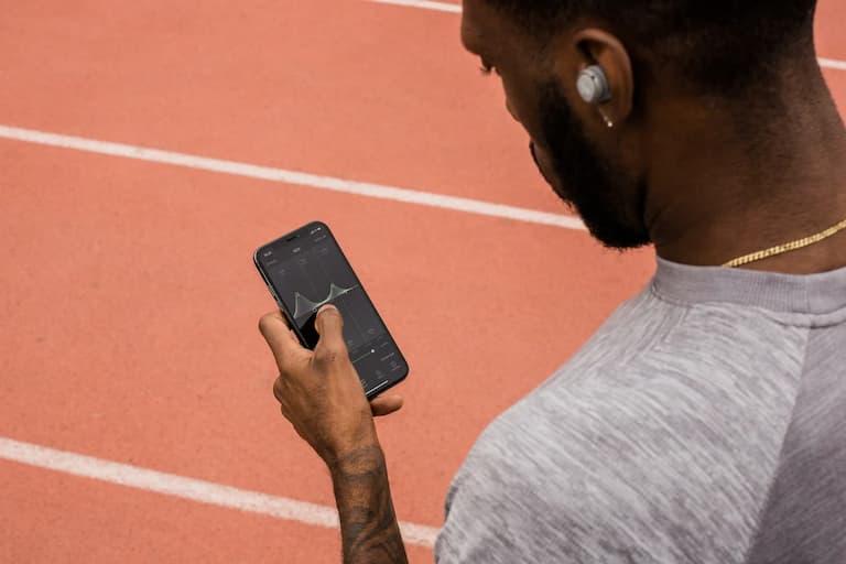 man on track using phone and jaybird headphones