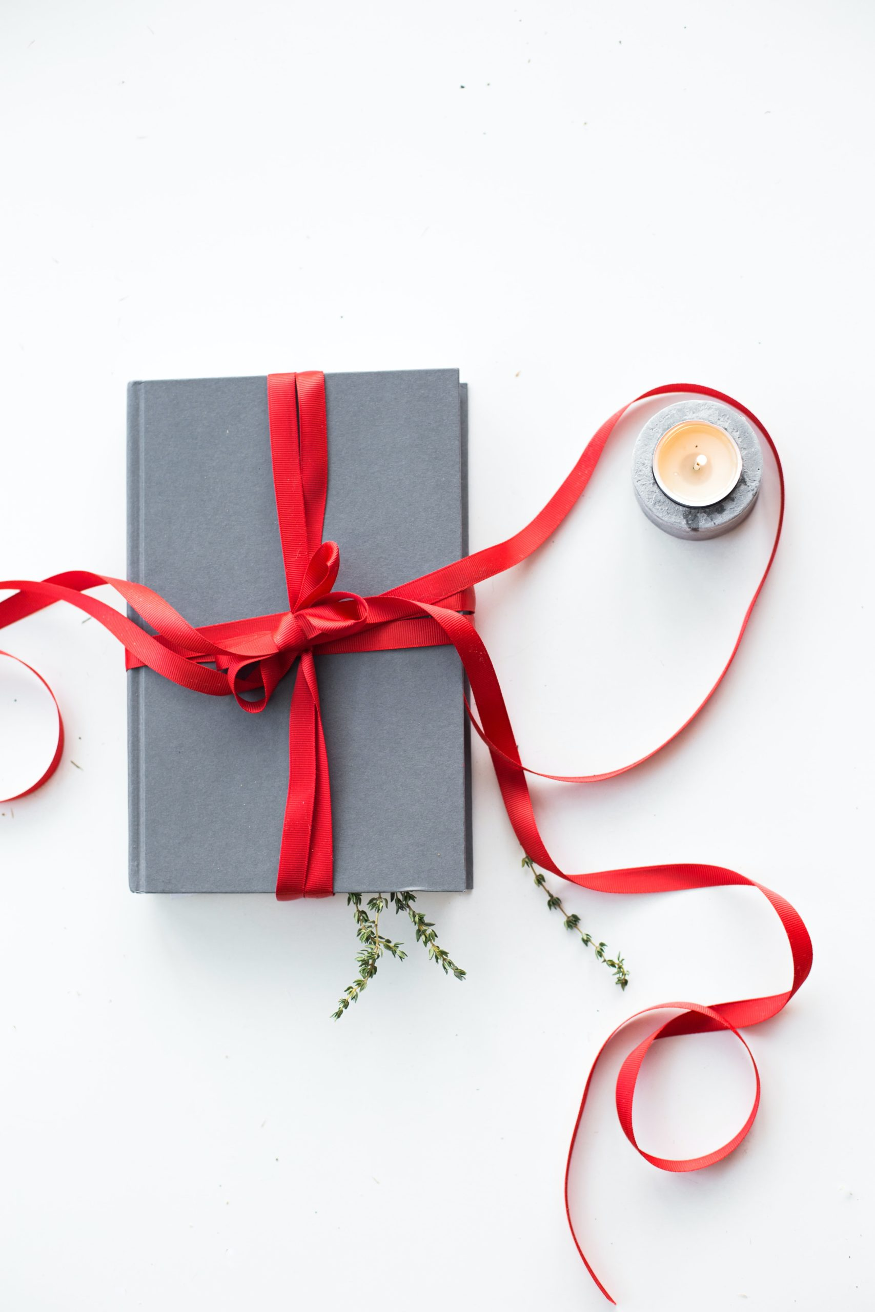 Grey notebook wraped with a red ribbon next to a tea light candle